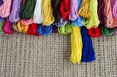 Colored Skeins Of Thread Lie On A Natural Linen Background Top, Blue Yellow Accentuated, Text Copy