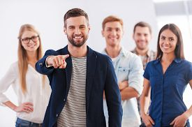 image of stand up  - Beautiful young woman showing her thumb up and smiling while group of happy young people standing on background and smiling - JPG