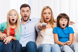 picture of bonding  - Surprised family of four bonding to each other and keeping mouth open while watching TV at home together - JPG