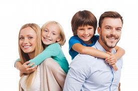 stock photo of bonding  - Happy family of four bonding to each other and smiling while standing against white background - JPG
