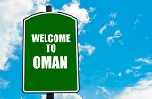 picture of oman  - Green road sign with greeting message WELCOME TO OMAN isolated over clear blue sky background with available copy space - JPG