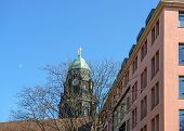 image of hercules  - Skyline view of old Baroque tower topped by Hercules statue above roof of New Town Hall behind naked winter tree from the corner of alley Kramergasse and Pfarrgasse in afternoon sunlight in Dresden Saxony Germany - JPG