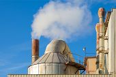 stock photo of smoking  - Smoking chimneys of a factory against a blue sky - JPG