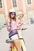 image of tandem bicycle  - A picture of two girl friends riding a tandem bicycle in the city - JPG
