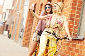 foto of tandem bicycle  - A picture of two girl friends riding a tandem bicycle and taking selfie in the city - JPG