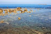 picture of tide  - seascape with low tide and fisherman in the background over surfacing rocks  - JPG