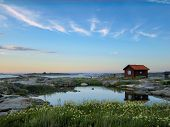 foto of reflection  - Small red wooden hut on a rocky skerry in the outer archipelago of Stockholm Sweden - JPG