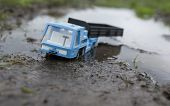 picture of mud  - Toy truck stuck in the mud concept of driving in a bad weather - JPG