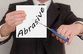 stock photo of abrasion  - Abrasive man in suit cutting text on paper with scissors - JPG