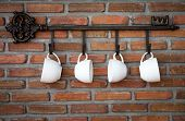 image of hook  - Coffee cups hanging on hooks in front of brick wall - JPG