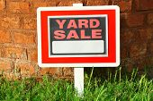 foto of yard sale  - Wooden Yard Sale sign in green grass on red brick wall background - JPG