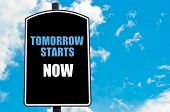 stock photo of start over  - TOMORROW STARTS NOW motivational quote written on road sign isolated over clear blue sky background with available copy space - JPG