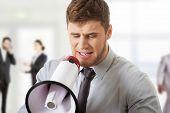 stock photo of shout  - Handsome businessman shouting through megaphone - JPG