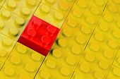 Red building block in a field of yellow ones