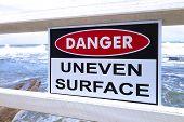 image of slip hazard  - A danger sign warning about an uneven surface near an Australian beach - JPG