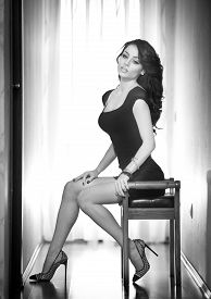 foto of short legs  - Attractive sexy brunette with long legs sitting on a chair with daylight in background - JPG