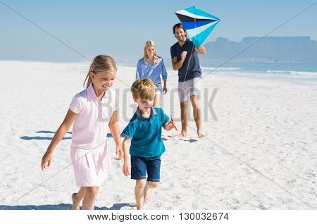 Happy family running at beach with blue kite. Family playing with kite in a summer vacation. Smiling