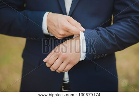Close-up Of Elegance Male Hands Wearing Modern Suit