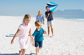 Happy family running at beach with blue kite. Family playing with kite in a summer vacation. Smiling poster