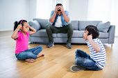 Annoyed father sitting on sofa while kids fighting and teasing each other at home poster
