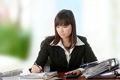 Ejecutivo mujer llenando los formularios mientras estaba sentado en su escritorio.