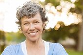 Portrait of senior woman relaxing at park. Close up face of happy senior woman looking at camera. Po poster