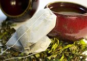 Two Teabags Lean Against a Traditional Asian Tea Cup