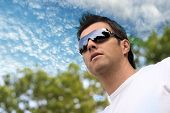 Young man wears futuristic sunglasses and looks at the future.