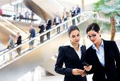 Two young businesswomen sharing text message on mobile phone in lobby, with businessmen traveling on
