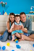 Portrait of happy family at home. Baby boy ( 1 year old ) and young parents father and mother sittin