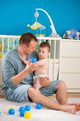 Young father sitting on floor and cuddling baby boy ( 1 year old ) at home in children's room, smili