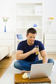 Casual young man using laptop computer at home, sitting at floor, drinking orange juice.