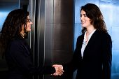Smiling business people shaking hands at office lobby in front of elevator.