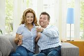 Excited couple watching TV at home, sitting on couch, holding remote control in hand.