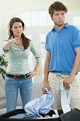 Unhappy couple fighting. Woman pointing out, man packing his clothes.