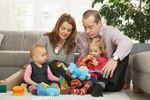 stock photo of nuclear family  - Happy family with two children playing on floor in living room at home sitting on floor in front of sofa - JPG