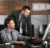 Two businessmen working together with computer at office desk, looking at screen.