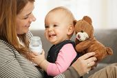 Happy mum and baby girl laughing cuddling holding teddy bear.