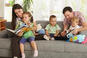 stock photo of family fun  - Happy nuclear family with three children having fun sitting on sofa at home - JPG