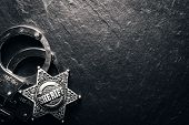 Sheriff star and handcuffs on black slate table closeup. Law concept background poster