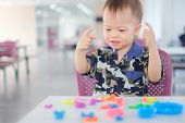 Cute Smiling Little Asian 18 Months Old Toddler Baby Boy Child Having Fun Playing Modeling Clay / Pl poster