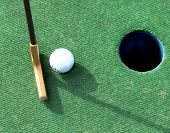 pic of miniature golf  - A putter and a white golf ball lined up with the hole on green - JPG