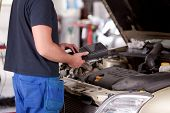 picture of internal combustion  - Detail of a mechanic using electrnoic diagnostic equipment to tune a car - JPG
