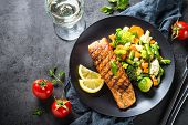 Grilled Salmon Fish Fillet With Vegetables Mix. Top View On Dark Stone Table. poster