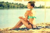 Suntan Lotion. Beauty young Woman Applying Sunscreen Solar Cream. Beautiful happy cute Girl applying poster