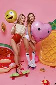 Playful Girls. Full Length Of Two Attractive Young Women In Swimwear Holding Balloons And Looking At poster