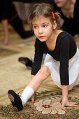 little girl in ballet class sits on string on floor with carpet