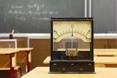 Educational galvanometer with not real number 555 on yellow desk in empty physics school class; form