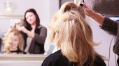 Beautiful Smiling Girl With Blond Wavy Hair By Hairdresser. Hairstylist Combing Female Client Young  poster