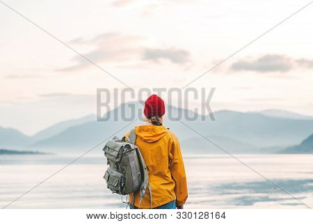 poster of Back View Of Male Tourist With Rucksack Standing On Coast In Front Of Great Mountain While Journey.